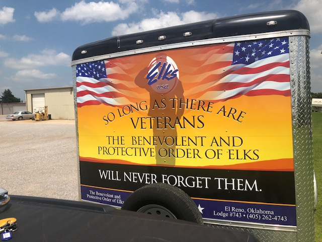 Trailer with soldier standing between US flags wrap